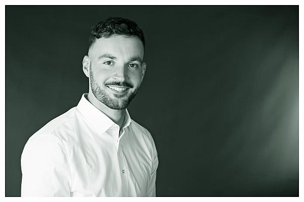 Low Key Bewerbungsfoto Mann in weißem Hemd vor dunklem Hintergrund, der lächelnd in die Kamera blickt.