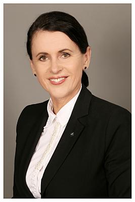 Bewerbungsfoto Frau mit Zopf vor grauem Hintergrund.