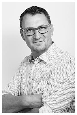 Low Key Bewerbungsfoto Mann mit Brille in hellem Hemd vor hellem Hintergrund.