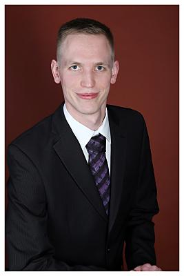 Bewerbungsfoto Mann in hellem Hemd und Schlips vor rotem Hintergrund.