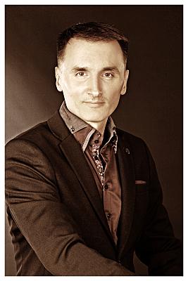 Low Key Bewerbungsfoto Mann in Hemd vor dunklem Hintergrund, der ernst in die Kamera blickt.