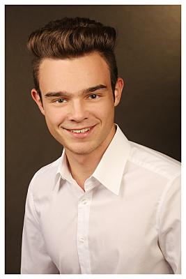 Bewerbungsfoto junger Mann in weißem Hemd vor dunklem Hintergrund.