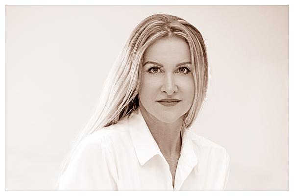 Low Key Bewerbungsfoto Frau mit offenen, blonden Haaren und weißem Hemd vor hellem Hintergrund.