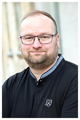 Bewerbungsfoto Mann mit Brille in hellem Hemd und Schlips vor Hausfassade.