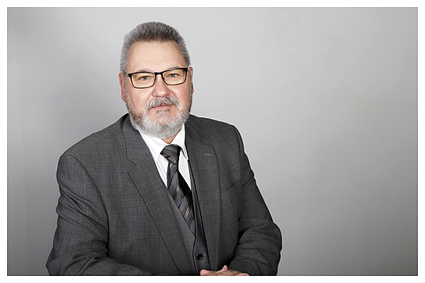Bewerbungsfoto Mann mit Brille in Hemd, Jacket und mit Schlips vor grauem Hintergrund.