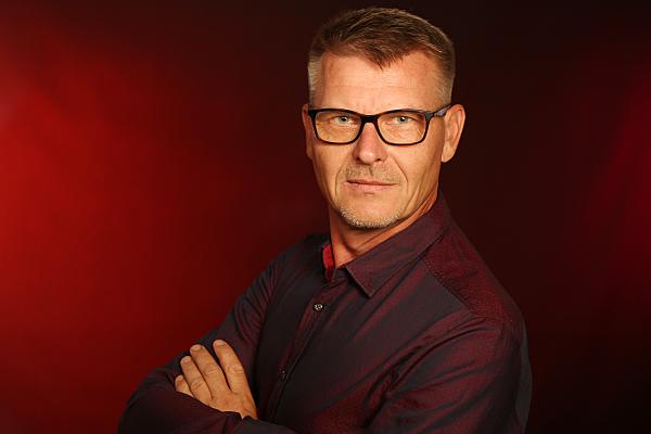 Businessfoto Mann mit Brille und verschränkten Armen vor dunklem Hintergrund.