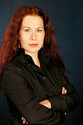 Businessfoto Frau mit offenen, rötlichen Haaren vor dunklem Hintergrund.