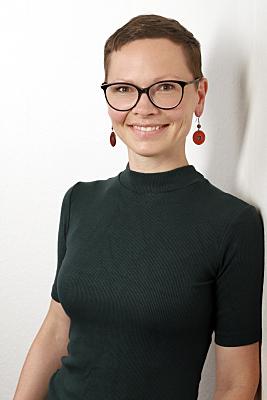 Businessfoto Frau mit Brille und kurzen Haaren in dunklem Pulli vor hellem Hintergrund.