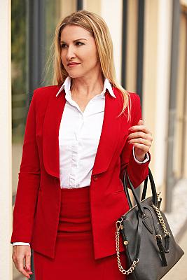 Businessfoto Frau mit dunkler Handtasche in heller Bluse und rotem Jacket vor einer Hausfassade.
