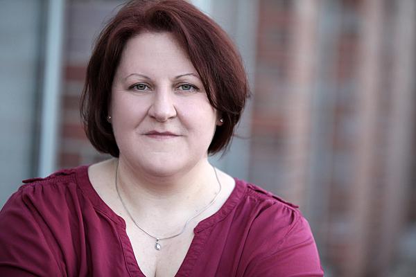 Businessfoto Frau in rotem Hemd vor Hausfassade.