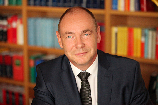 Businessfoto Mann in hellem Hemd mit Schlips und dunklem Jacket vor einer Bücherwand.
