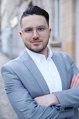 Businessfoto junger Mann mit Brille in hellem Hemd und blauen Jacket vor Hausfassade.