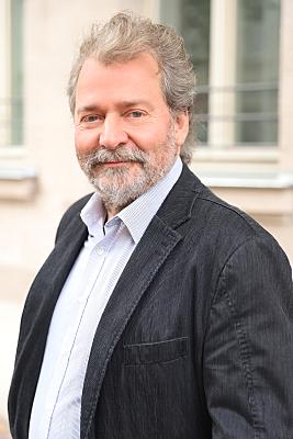 Businessfoto Mann in hellem Hemd und Jacket vor Hausfassade.