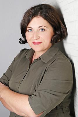 Businessfoto Frau mit kurzem Haar und roten Lippen vor grauem Hintergrund.
