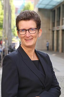 Businessfoto Frau mit Brille und dunklem Hemd vor Hausfassade.