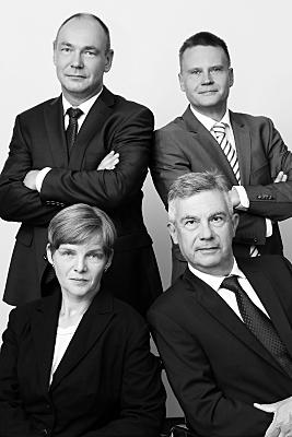 Low Key Businessfoto drei Geschäftsmänner und eine Geschäftsfrau mit vor der Brust verschränkten Armen.