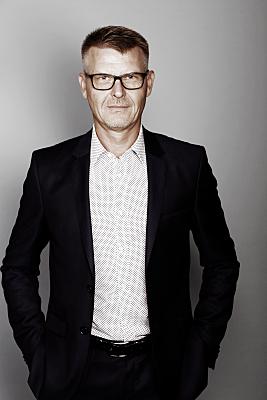 Businessfoto Mann mit Brille in hellem Hemd und dunklem Jacket vor grauem Hintergrund.
