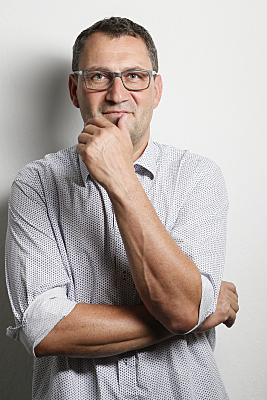 Businessfoto Mann mit Brille in hellem Hemd vor grauem Hintergrund, der seine Hand ans Kinn hält.