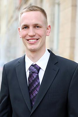 Businessfoto Mann in hellem Hemd und Schlips vor Hausfassade.