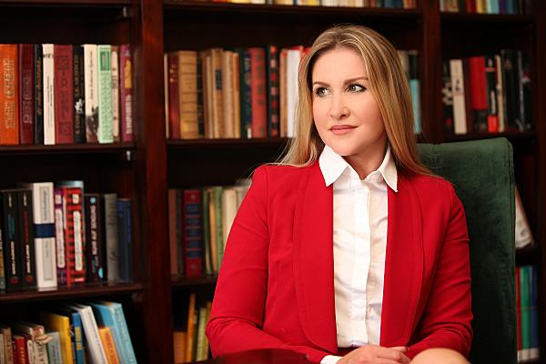 Businessfoto Frau in heller Bluse und rotem Jacket vor einer Bücherwand.