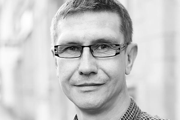 Low Key Businessfoto Mann mit Brille in Hemd vor Hausfassade.