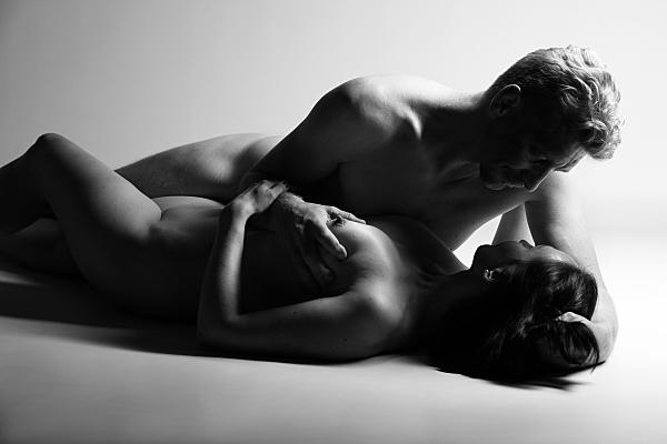 Schwarz-weißes Aktfoto Paar, bei dem beide auf dem Boden liegen, während der Mann sich über die Frau beugt und ihre Brust von mit der Hand anhebt.