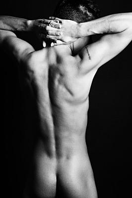 Schwarz-weiß Aktfoto nackter Männeroberkörper und Po mit im Nacken gefalteten Händen.