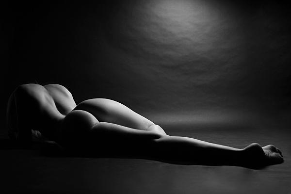 Schwarz-weiß Aktfoto einer auf dem Bauch liegenden Frau vor schwarzem Hintergrund.