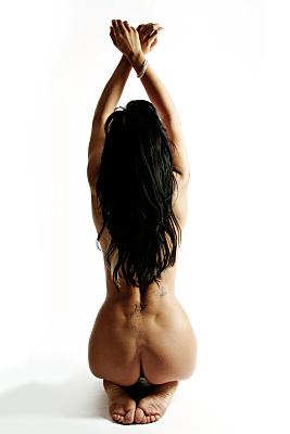 Aktfoto einer sitzenden Frau mit langem, dunklen Haar, die ihre Arme in die Luft reckt in Rückansicht.