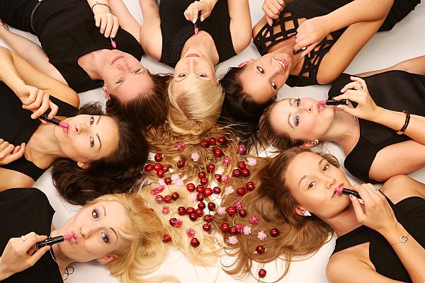 Freundefoto sieben lächelnde, auf dem Rücken mit den Köpfen einen Kreis bildend liegende Frauen mit Kirschen in der Mitte und Lippenstiften in den Händen.