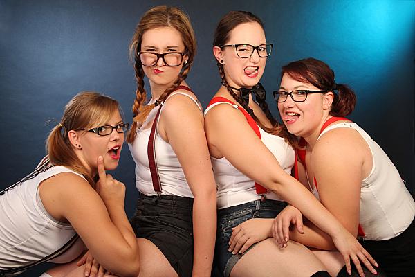 Freundefoto vier lächelnder Frauen in weißen Tops mit kurzen Hosen und Hosenträgern vor blauem Hintergrund.