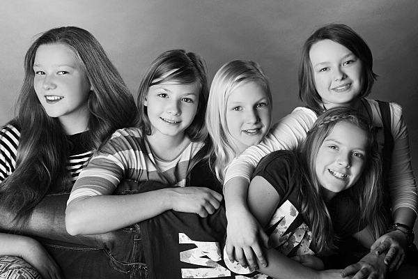 Low Key Freundefoto fünf Frauen, die nebeneinander sitzen und sich umarmen.
