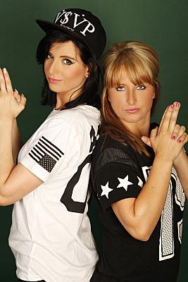 Freundefoto zweier ernst blickender Frauen, die ihre Hände zu Pistolen formen, vor dunklem Hintergrund.