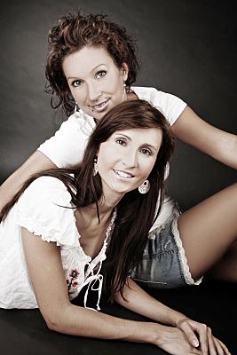 Low Key Freundefoto zwei Frauen, die voreinander vor einem dunklen Hintergrund sitzen.