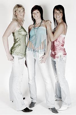 Freundefoto drei Frauen nebeneinander stehend in hellen Hosen und blumigen Oberteilen.