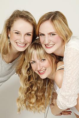 Freundefoto drei Frauen in hellen Oberteilen, die sich ins Bild neigen.