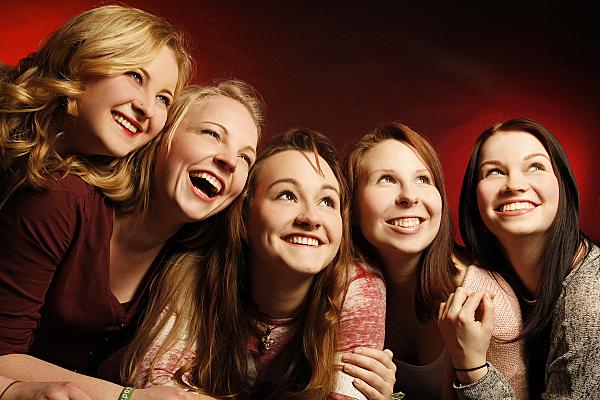 Freundefoto fünf junge Frauen, die nebeneinander stehen und nach oben schauen vor rotem Hintergrund.