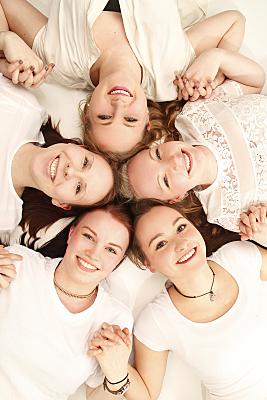 Freundefoto fünf auf dem Rücken liegende Frauen, die sich an den Händen halten.
