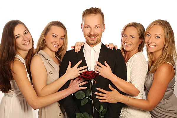 Freundefoto vier stehende Frauen, die einen Mann in ihrer Mitte berühren.