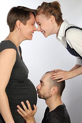 Foto Babybauch Schwangere, deren Bauch der Partner küsst und deren ältere Tochter ihre Stirn an ihren Kopf lehnt.