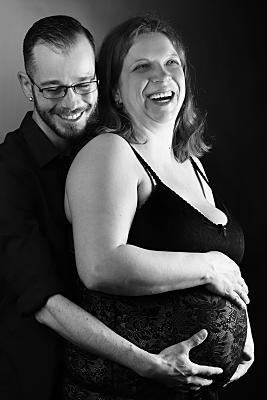 Schwarz-weiß Foto Babybauch Schwangere und diese von hinten umarmender Partner.