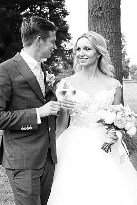 Low Key Hochzeitsfoto sich gegenüber stehendes, mit Sekt anstoßendes, Brautpaar.