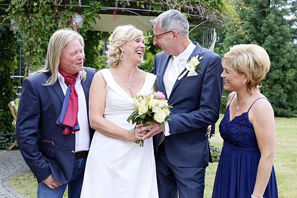 Hochzeitsfoto sich anschauendes Brautpaar zwischen Mann und Frau.Gästen.