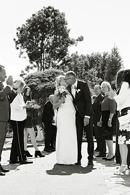 Low Key Hochzeitsfoto küssendes Brautpaar vor Gästen.