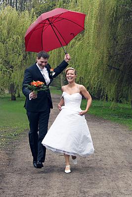 Hochzeitsfoto Brautpaar nebeneinander unter rotem Regenschirm stehend.