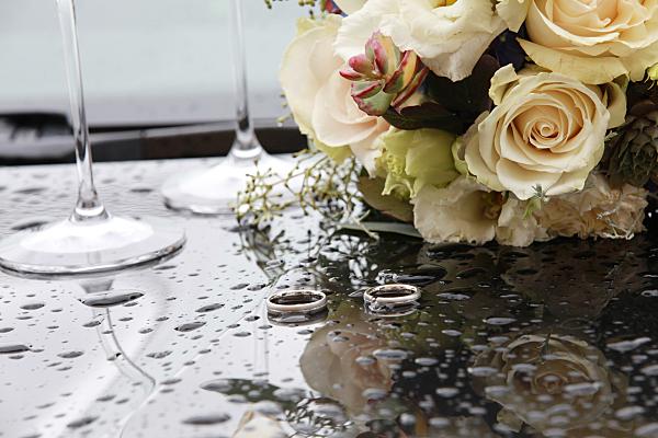 Hochzeitsfoto Brautstrauß auf Tisch mit Eheringen und Sektkelchen.