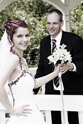 Hochzeitsfoto Brautpaar mit zwischen den beiden gehaltenem Brautstrauß.