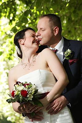 Hochzeitsfoto küssendes Brautpaar  vor Bäumen.
