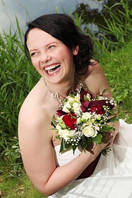Hochzeitsfoto lachende Braut mit Brautstrauß.