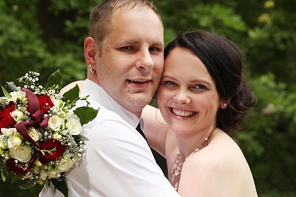 Hochzeitsfoto sich umarmendes Brautpaar vor Bäumen.